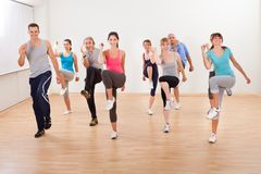 Group of people doing aerobics exercises. Large diverse group of people doing aerobics exercises in a class in a gym in a health and fitness concept royalty free stock photo