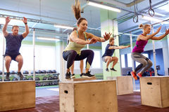 Group of people doing box jumps exercise in gym Stock Photo