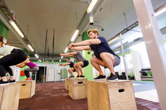 Group of people doing box jumps exercise in gym Royalty Free Stock Image