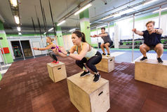 Group of people doing box jumps exercise in gym Royalty Free Stock Photos
