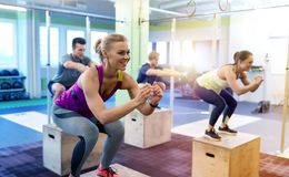 Group of people doing box jumps exercise in gym. Fitness, sport, training and exercising concept - group of people with heart-rate trackers doing box jumps in Stock Photos