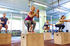 Group of people doing box jumps exercise in gym Stock Image