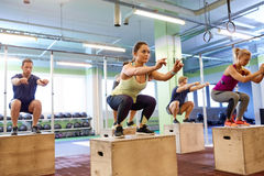 Group of people doing box jumps exercise in gym Royalty Free Stock Photo