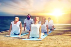 Group of people doing cobra pose outdoors Stock Photo