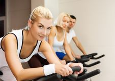Group of people doing exercise. On a bike in a gym stock photography