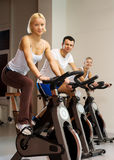 Group of people doing exercise. On a bike in a gym Stock Images