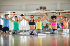 Group of people doing exercise with resistant rubber. Group of young people doing exercise with resistant rubber in gym royalty free stock image