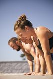 Group of people doing push-ups on beach Royalty Free Stock Photography
