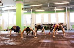 Group of people doing push-ups in gym Stock Image