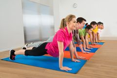 Group of people doing push ups royalty free stock image