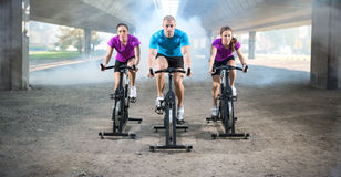 Group of people doing spinning on cycle bike. Outdoor Royalty Free Stock Images