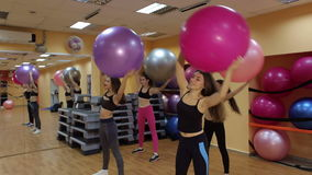 Group of people doing stretching exercise with fitness balls in hands. stock video