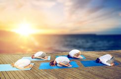 Group of people doing yoga child pose outdoors Royalty Free Stock Image