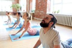 Group of people doing yoga cobra pose at studio Stock Photo