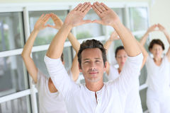 Group of people doing yoga  exercises Stock Photos