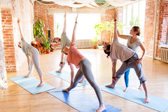 Group of people doing yoga exercises at studio. Fitness, sport and healthy lifestyle concept - group of people with personal trainer doing yoga exercises on mats Royalty Free Stock Photography