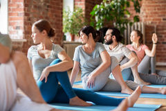 Group of people doing yoga exercises at studio. Fitness, sport and healthy lifestyle concept - group of people doing yoga seated spinal twist pose in gym or Royalty Free Stock Photography