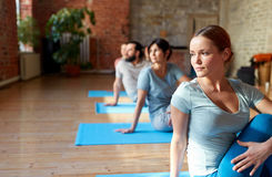 Group of people doing yoga exercises at studio. Fitness, sport and healthy lifestyle concept - group of people doing yoga seated spinal twist pose in gym or Stock Images