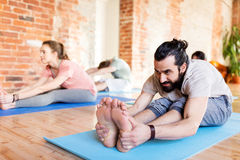 Group of people doing yoga forward bend at studio. Fitness, sport and healthy lifestyle concept - group of people doing yoga seated forward bend pose on mats at Royalty Free Stock Photo