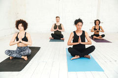 Group of people doing yoga in gym sitting on training mats stock photo