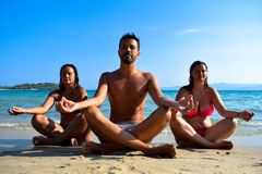 Relaxed people exercising Yoga on the beach in summer day. stock image