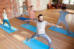 Group of people doing yoga warrior pose at studio. Fitness, sport and healthy lifestyle concept - group of people doing yoga in warrior pose at studio Stock Images