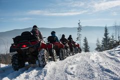Group of people driving four-wheelers ATV bikes on snow in winter. Group of people driving four-wheelers ATV bikes on snow at top of the mountain in winter Stock Photography