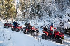 Group of people driving off-road four-wheelers ATV bikes in winter forest Stock Photo