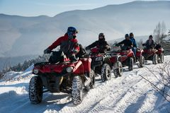 Group of people driving off-road quad bikes on snow in winter. Group of people driving off-road quad bikes on snow at top of the mountain in winter Stock Images