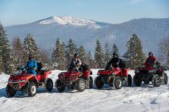 Group of people driving quad bikes at top of the mountain in winter Stock Photos