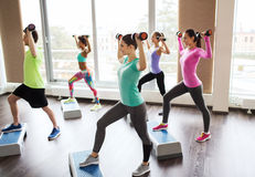 Group of people with dumbbells and steppers stock images
