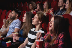 Group of people enjoying movie at the cinema. Group of people looking excited while watching a movie at the cinema audience lifestyle leisure happiness emotions Stock Image