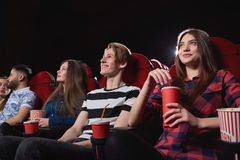 Group of people enjoying movie at the cinema. Low angle shot of happy young people smiling enjoying watching a movie at the cinema comedy premiere film Royalty Free Stock Images