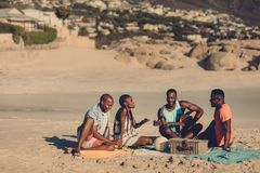 Group of people enjoying at the seaside picnic. Group of friends with guitar sitting on beach. African people enjoying at the seaside picnic royalty free stock photo