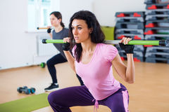 Group of people excercising with bars in gym doing squatting a barbell at fitness club Stock Images