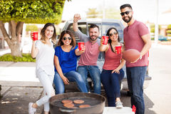Group of people excited about a footbal game. Young Hispanic friends celebrating the victory of their football team while drinking and having fun at a barbecue royalty free stock photo