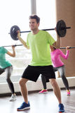 Group of people exercising with barbell in gym Stock Images