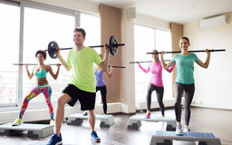 Group of people exercising with barbell in gym Stock Photo