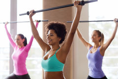 Group of people exercising with bars in gym Stock Photos