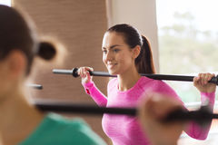 Group of people exercising with bars in gym Stock Photo
