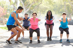 Group Of People Exercising InStreet With Personal Trainer Stock Image