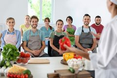 Group of people and female chef. At cooking classes stock image