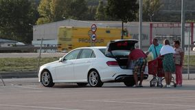 Group of people filling the trunk of their car with goods bought in a shopping mall in Spain. Group of people filling the trunk of their car with goods bought stock footage