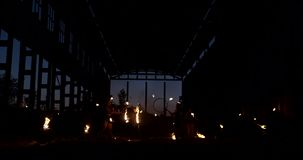A group of people with fire and torches dancing at sunset in the hangar in slow motion. Fire show stock video footage