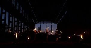 A group of people with fire and torches dancing at sunset in the hangar in slow motion. Fire show stock footage