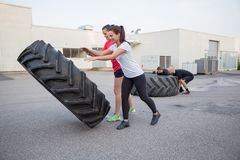 Group of people flipping heavy tires as workout Stock Image