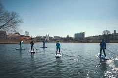 A group of people floating on the paddle boards in the background of the city, outdoor activities on the water, the city of Minsk royalty free stock photography
