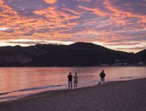 Group of people flying a drone during beautiful blue pink orange clouds sunset on Agios Georgios Pagon beach at Corfu stock photos