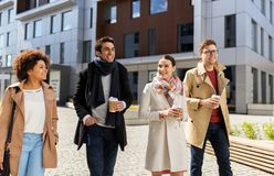 Group of people or friends with coffee in city. Business, lifestyle and corporate concept - international group of people or friends with coffee on city street royalty free stock photos