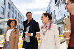 Group of people or friends with coffee in city. Business, lifestyle and corporate concept - international group of people or friends with coffee on city street stock image